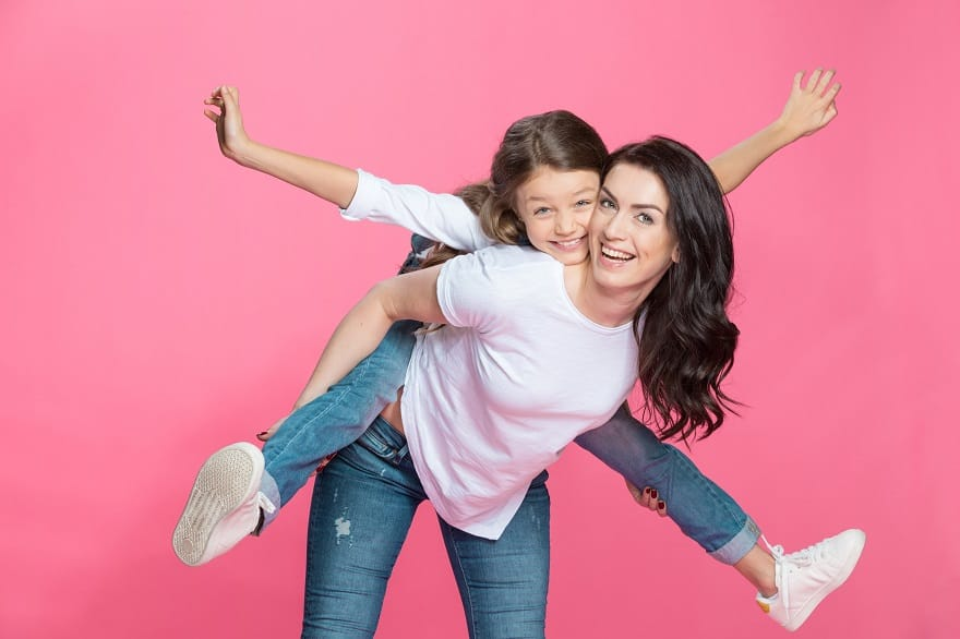 Happy mother piggybacking adorable little daughter