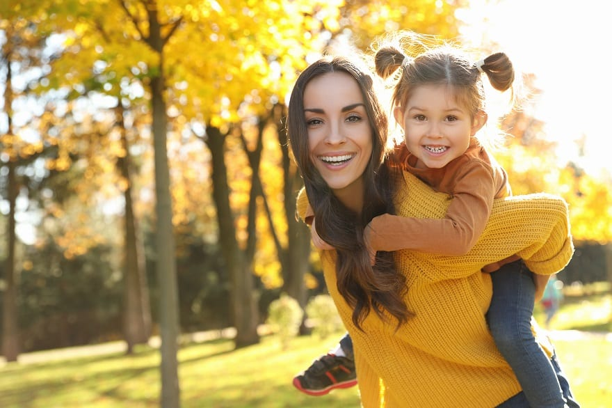Moving to France Happy woman with little daughter in sunny park. Autumn walk