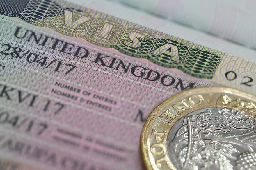 Moving to the UK - United Kingdom visa in the passport with one pounds coin