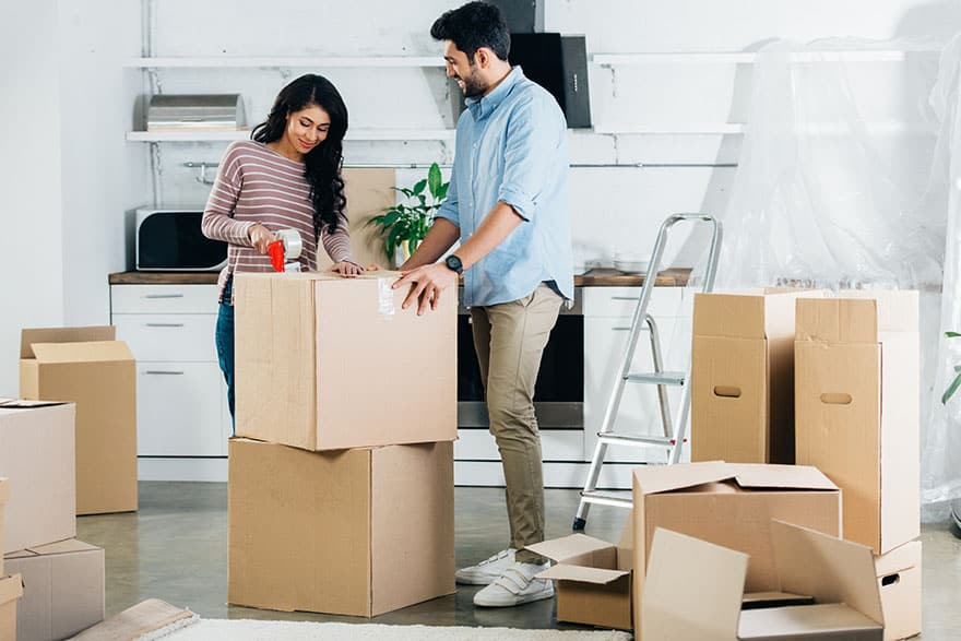 indian couple packing boxes while moving to new home